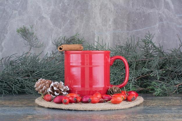 Filiżanka kawy z owocami dzikiej róży i szyszkami na marmurowym tle. zdjęcie wysokiej jakości