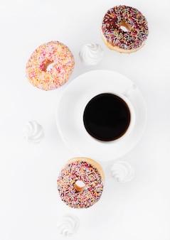 Filiżanka kawy z pączkami i bezy w ruchu