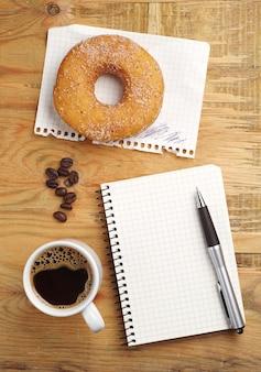 Filiżanka kawy z pączkiem i notatnikiem