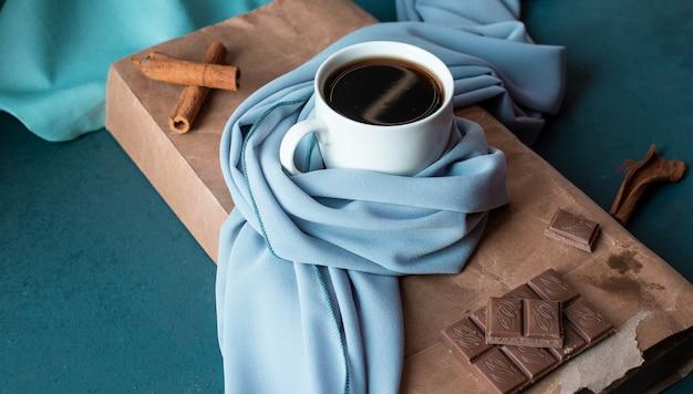 Filiżanka kawy z paluszkami cynamonu i tabliczką czekolady.