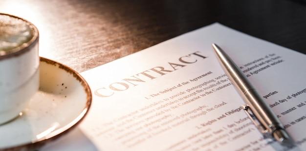 Filiżanka kawy z pianką i cynamonem, długopis, pusta umowa na drewnianym stole.