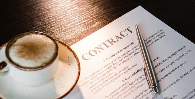 Filiżanka kawy z pianką, srebrny długopis i pusta umowa na drewnianym stole.