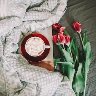 Filiżanka kawy z piankami i czerwonymi tulipanami w łóżku. koncepcja wakacji, urodzin, walentynki, 8 marca