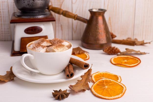 Filiżanka kawy z piankami i kakao, liście, wysuszone pomarańcze, pikantność, na białym tle. pyszny gorący jesienny napój, poranny nastrój. copyspace.