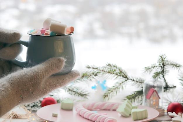 Filiżanka kawy z piankami w dłoniach w rękawiczkach na tle świątecznej dekoracji