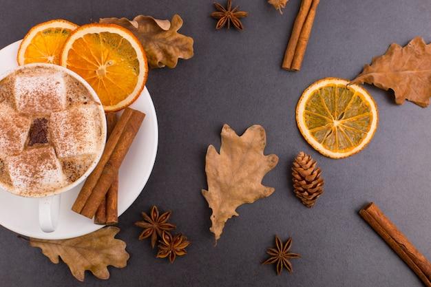Filiżanka kawy z pianki i kakao, liście, suszone pomarańcze, cynamon i anyż, szary kamień tło. smaczny gorący napój jesienny. copyspace.