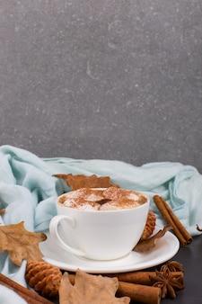 Filiżanka kawy z pianki, kakao, szalik, liście, suszone pomarańcze, przyprawy, na szarym tle. pyszny gorący jesienny napój, poranny nastrój. copyspace.
