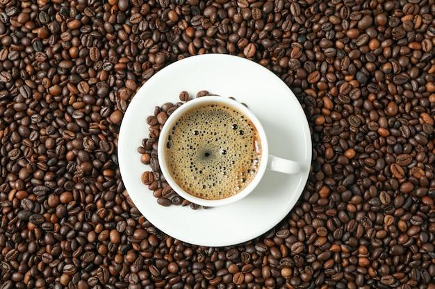 Filiżanka kawy z piankowatą pianą na fasoli tle