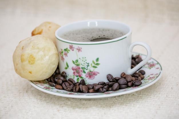 Filiżanka kawy z pieczywem serowym i ziarnami kawy z boku