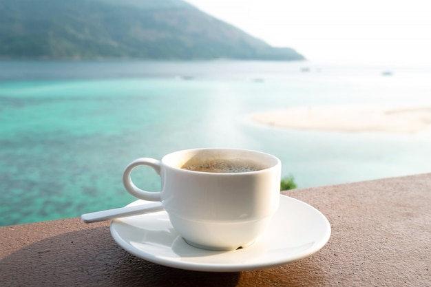 Filiżanka kawy z piękną plażą w okresie letnim. podróże koncepcyjne, wakacje i wakacje. natura krajobraz przy lipe wyspą w tajlandia