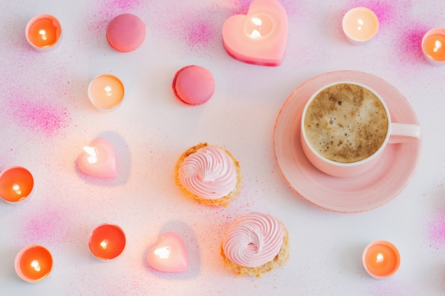 Filiżanka kawy z płonącymi świeczkami na różowo malowanej powierzchni papieru