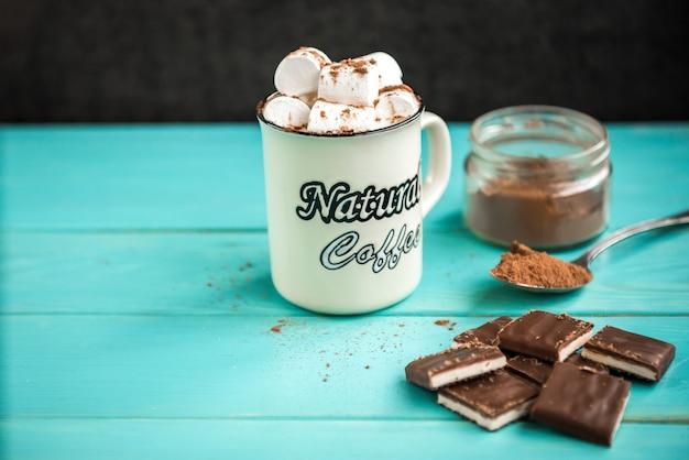 Filiżanka kawy z ptasie mleczko, dzianinowy niebieski szalik, tabliczka czekolady i kakao na zielonym tle drewnianych. napoje i słodycze.