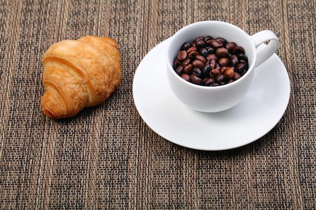 Filiżanka kawy z rogalika i świeżych ziaren kawy na brązowym tle