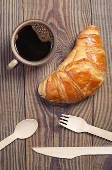Filiżanka kawy z rogalikiem i drewnianymi sztućcami na drewnianym stole