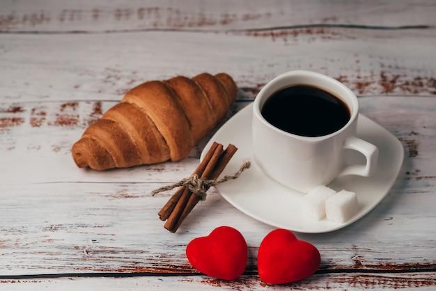 Filiżanka kawy z rogalikiem i serca na drewnianym stole. pojęcie rano śniadanie w walentynki
