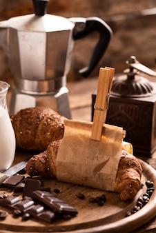 Filiżanka kawy z rogalikiem i świeżą kawą na brązowym tle