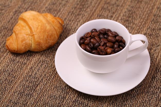 Filiżanka kawy z rogalikiem i świeżymi ziarnami kawy