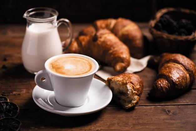 Filiżanka kawy z rogalikiem na rustykalnym drewnianym stole clse up