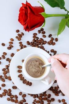 Filiżanka kawy z różą na białym tle. ziarna kawy są porozrzucane na stole.