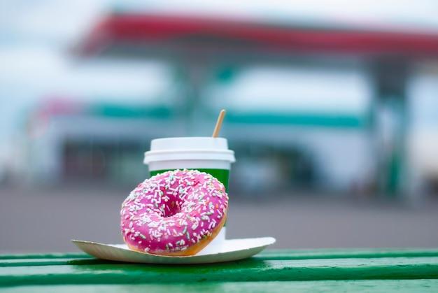 Filiżanka kawy z różowym pączkiem na tle stacji benzynowej.