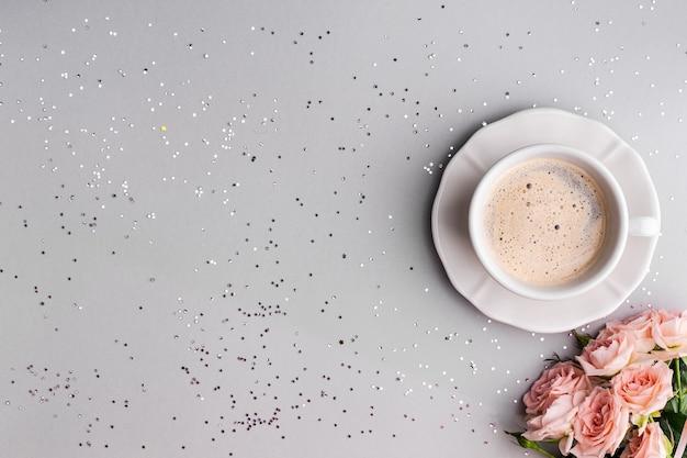 Filiżanka kawy z różowymi różami na świątecznej szarości