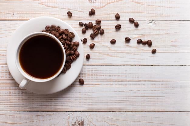 Filiżanka kawy z rozrzuconymi kawowymi fasolami na drewnianym stołowym tle. jesienny poranek nastrój, lato.