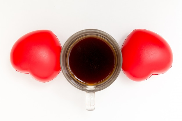 Filiżanka kawy z sercami na bielu stole.