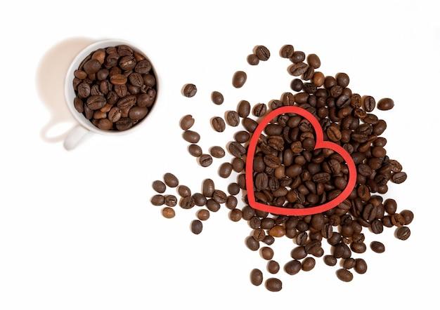 Filiżanka kawy z sercem z ziaren kawy na białym tle.