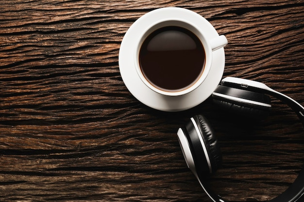 Filiżanka kawy z słuchawkami na drewnianym stole. widok z góry kawy z miejsca na kopię. koncepcja picia.