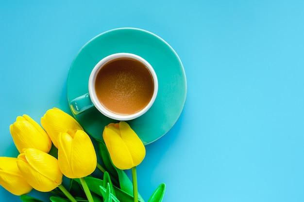 Filiżanka kawy z spodeczkiem i sztucznymi żółtymi tulipanami na błękitnym tle