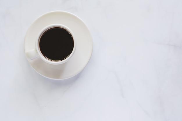 Filiżanka kawy z spodeczkiem na białym marmurowym tle dla napojów i napoju pojęcia
