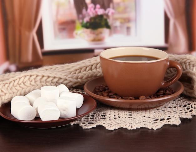 Filiżanka kawy z szalikiem na stole w pokoju