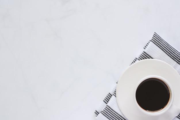 Filiżanka kawy z talerzykiem i napery na białym marmurowym tle dla napojów i napoju co