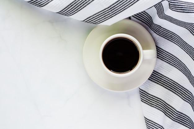 Filiżanka kawy z talerzykiem i napery na białym marmurowym tle dla napojów i napoju