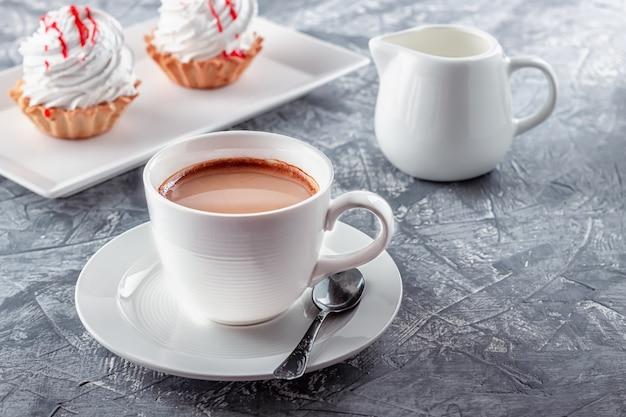 Filiżanka kawy z tartami z bitą śmietaną