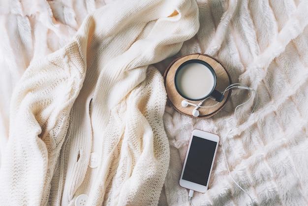 Filiżanka kawy z telefonem i słuchawkami, styl skandynawski