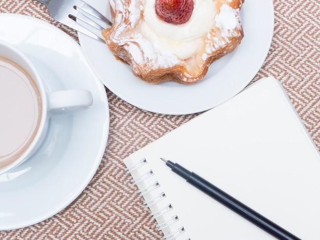 Filiżanka kawy z tortem i notatnikiem