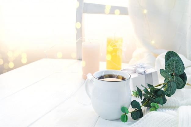 Filiżanka kawy z trykotowym szalikiem na zostawać na drewnianej tacy w łóżku, kopii przestrzeń. dzień dobry śniadanie