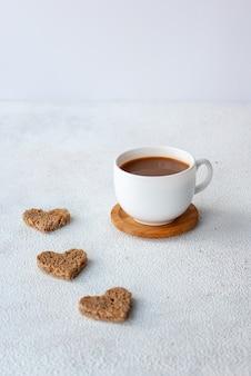 Filiżanka kawy z trzema kawałkami chleba w kształcie serca