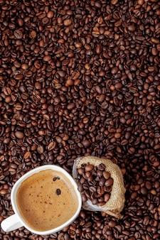 Filiżanka kawy z worek kawy na drewnianym stole. widok z góry