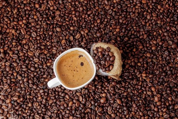 Filiżanka kawy z worek kawy na drewnianym stole.