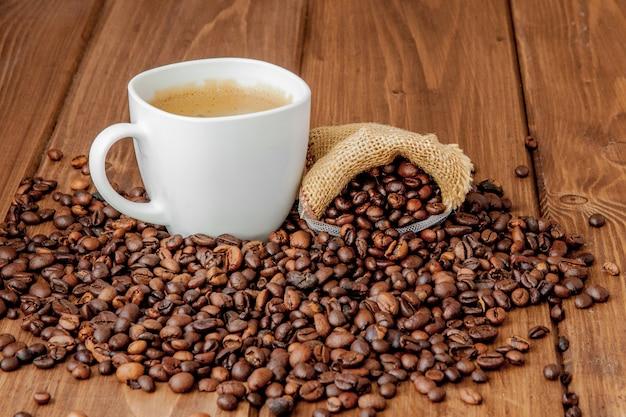 Filiżanka kawy z worek kawy na drewnianym stole