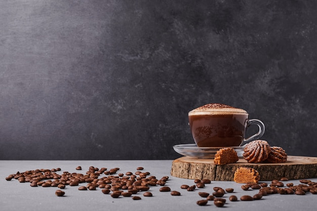 Filiżanka kawy z ziaren arabiki dookoła.