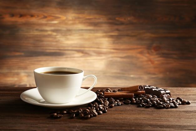 Filiżanka kawy z ziaren, czekolady i cynamonu na drewnianym stole