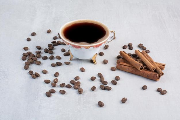 Filiżanka kawy z ziaren kawy i laskami cynamonu