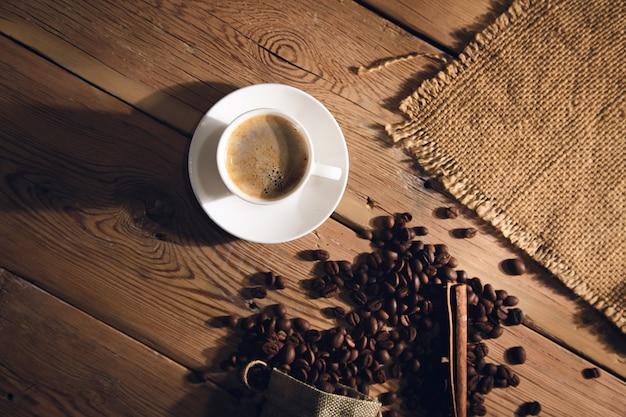 Filiżanka kawy z ziaren kawy i płótno z cynamonem