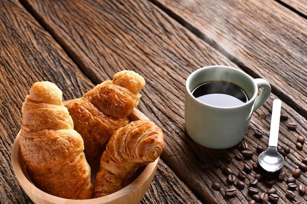 Filiżanka kawy z ziaren kawy i rogalika na drewnianym stole