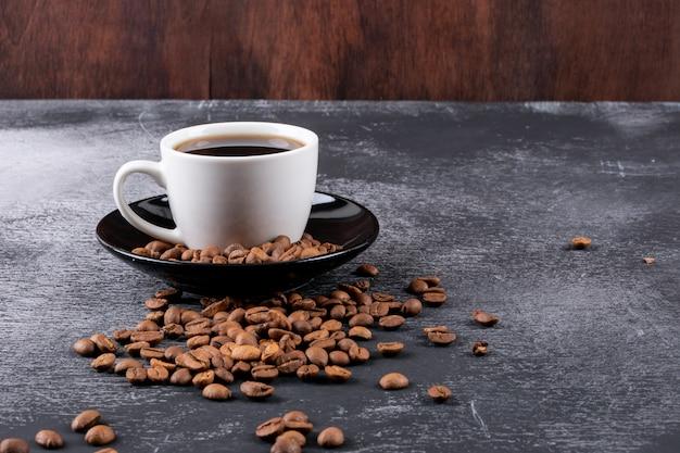Filiżanka kawy z ziaren kawy na ciemnym stole