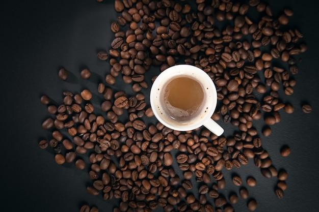 Filiżanka kawy z ziaren kawy na czarnym tle