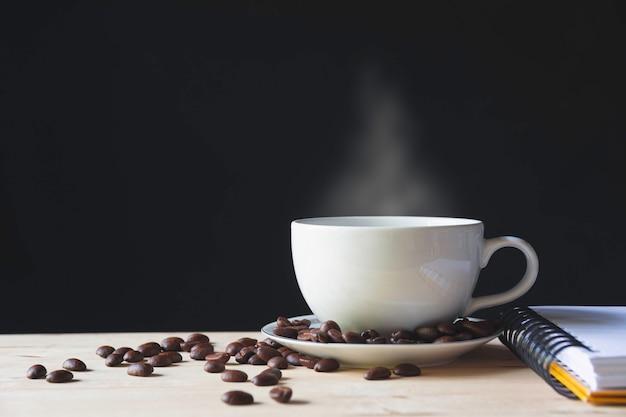 Filiżanka kawy z ziaren kawy na drewnianym stole